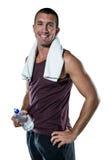 有毛巾的微笑的人在拿着水瓶的脖子 免版税图库摄影