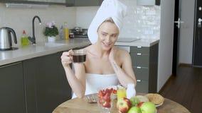 有毛巾的美女在食用的头一份健康早餐和咖啡 股票录像