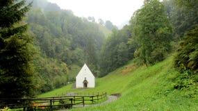 有毛毛雨和树的Flueli Ranft更低的教堂 免版税库存照片