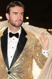 有毛皮夹克和金黄无尾礼服的时髦的人 库存图片