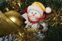 有毛皮树玩具和闪亮金属片的雪人 免版税库存图片