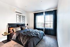 有毛皮毯子的豪华卧室在加长型的床上 免版税图库摄影