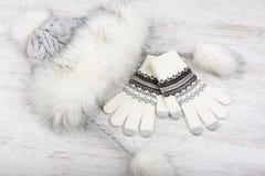 有毛皮的冬天帽子和在白色木背景的被编织的手套 免版税库存图片