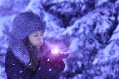 有毛皮盖帽的愉快的吹雪花的女孩和手套在冬天城市 免版税库存图片