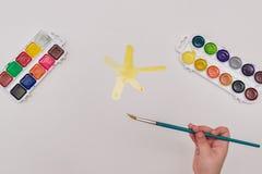 有毛笔画的儿童手在白皮书黄色太阳 免版税图库摄影