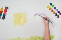 有毛笔画黄色太阳的儿童手在白皮书 免版税库存图片