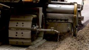 有毛虫轮子的机器虽则移动路 涂柏油的 股票录像