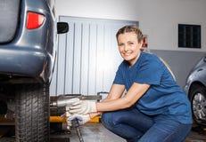 有气动力学的板钳的微笑的女性技工定象轮胎 免版税库存照片
