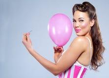 有气球和Pin的年轻感觉上的妇女 免版税库存图片