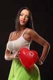 有气球心脏的华伦泰美丽的女孩在她的手上 免版税库存照片