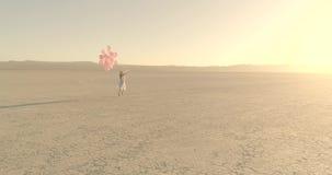 有气球的一个女孩走在沙漠湖El海市蜃楼的 空中寄生虫 2017年10月 影视素材