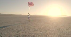 有气球的一个女孩走在沙漠湖El海市蜃楼的 空中寄生虫 2017年10月 股票录像