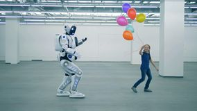 有气球的一个女孩跳舞,并且一个男人似机器人来临往她 股票视频
