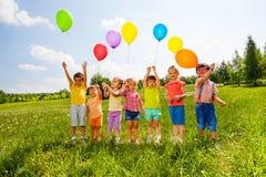有气球的七个孩子在绿色领域 免版税图库摄影