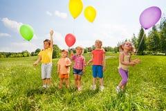 有气球的五个逗人喜爱的孩子在绿色领域 库存照片