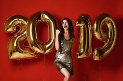有气球的令人惊讶的快乐的时髦的妇女庆祝除夕党的 免版税库存图片