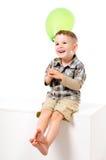 有气球的俏丽的笑的男孩 免版税库存图片
