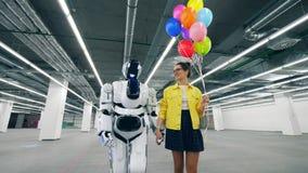 有气球的女孩和droid在屋子里走,握手 股票视频