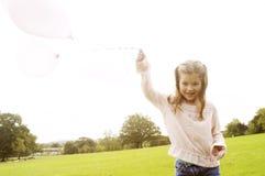 有气球的女孩在公园。 库存图片