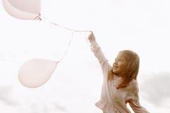 有气球的女孩在公园。 图库摄影