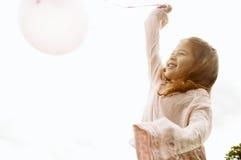有气球的女孩在公园。 免版税库存图片