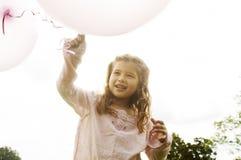 有气球的女孩在公园。 库存照片