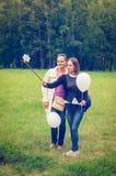 有气球的女孩在绿草的手机做selfie 图库摄影