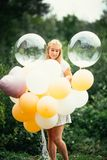 有气球的女孩在自然背景 免版税库存图片