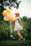 有气球的女孩在自然背景 库存照片