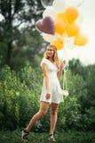 有气球的女孩在自然背景 图库摄影