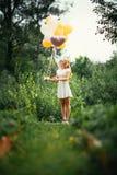 有气球的女孩在自然背景 库存图片