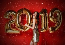 有气球的妇女庆祝党的 美丽的微笑的女孩画象获得发光的金黄的礼服的与金气球的乐趣 免版税库存照片