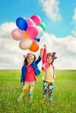 有气球的孩子走在春天领域的 免版税图库摄影