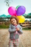 有气球的小女孩在含沙银行  免版税库存图片