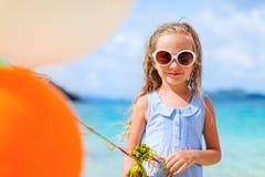 有气球的小女孩在海滩 免版税库存照片