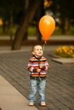 有气球的小滑稽的男孩 免版税库存图片