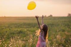 有气球的愉快的女孩在日落 免版税库存图片