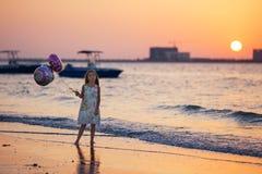 有气球的甜美丽的女孩在海上的日落 库存照片