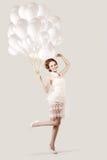 有气球的美丽的年轻时髦现代微笑的女孩在跃迁 免版税库存照片