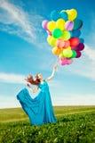 有气球的豪华时尚妇女在手中在领域反对 免版税库存图片