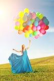 有气球的豪华时尚妇女在手中在领域反对 库存图片