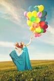 有气球的豪华时尚妇女在手中在领域反对 免版税库存照片