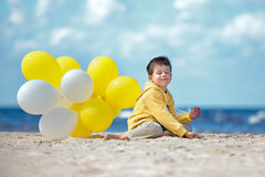 有气球的逗人喜爱的小男孩在海滩 库存图片