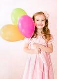 有气球的逗人喜爱的微笑的小女孩 免版税库存图片