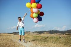 有气球的逗人喜爱的男孩 库存照片