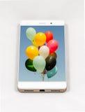 有气球的整个银幕的图片的现代智能手机在displa的 免版税库存图片