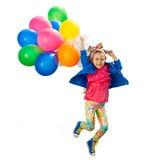 有气球跳跃的小女孩 免版税库存图片
