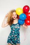 有氦气的十几岁的女孩迅速增加在灰色背景 库存图片