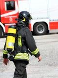 有氧气瓶和盔甲的意大利消防队员 库存照片
