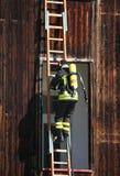 有氧气罐火的勇敢的消防队员在举行的锻炼期间 库存照片